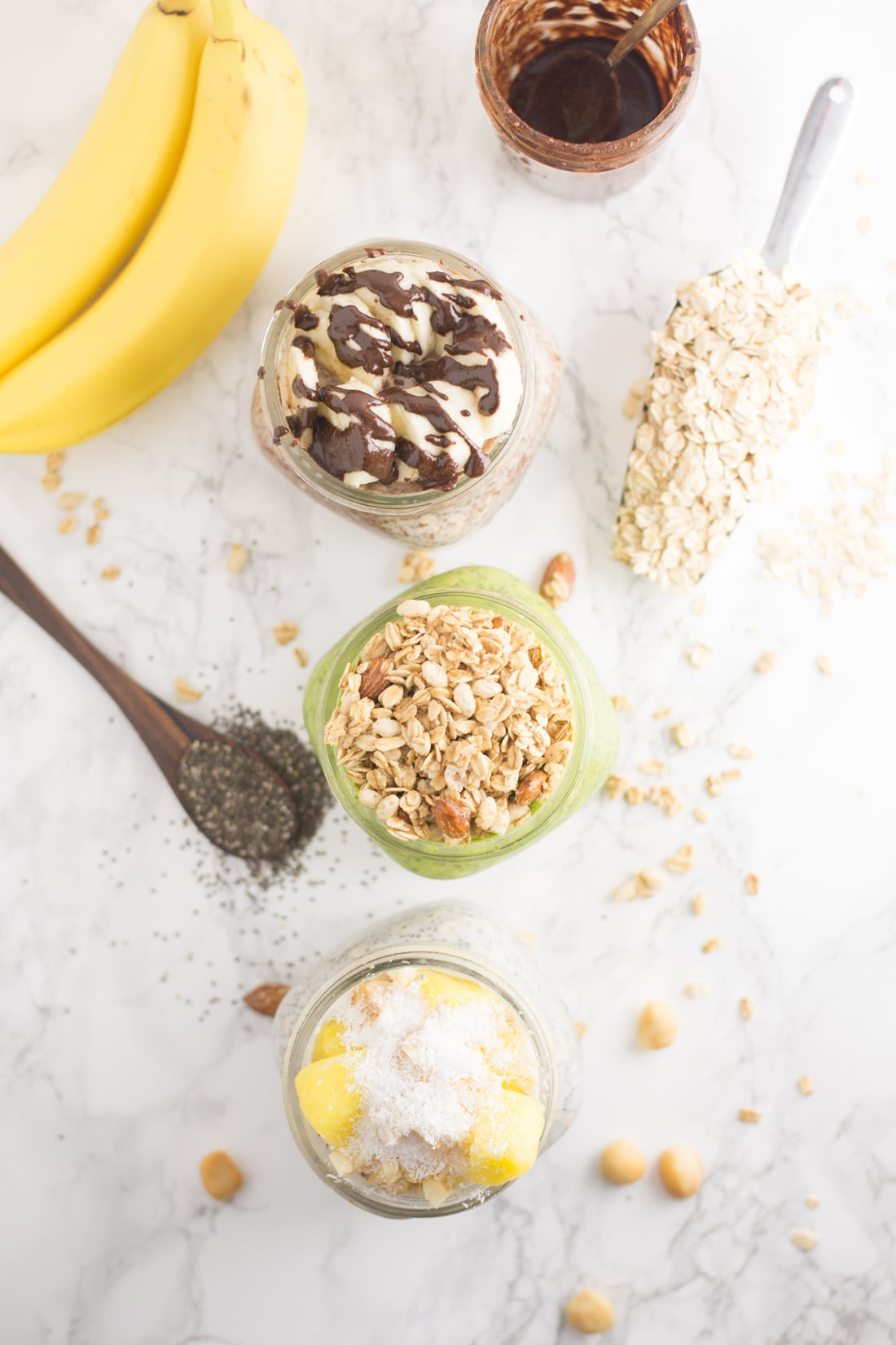 overhead photo of three mason jars with overnight oatmeal. Oats, bananas, macadamia nuts, chocolate and wooden spoon are on marble background.