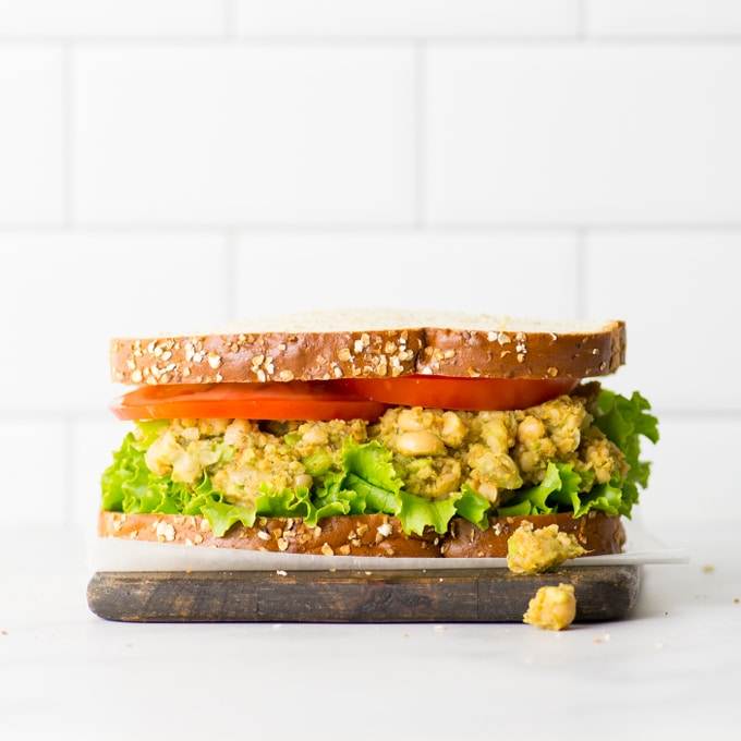 no mayo chickpea salad recipe. vegan sandwich on wood board.