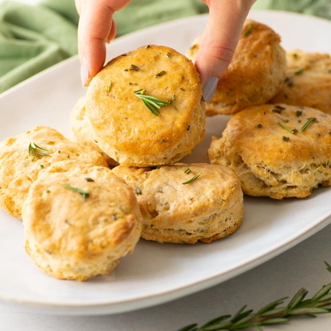 hands picking up vegan rosemary biscuit from platter