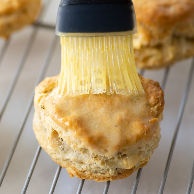 brushing butter onto biscuit