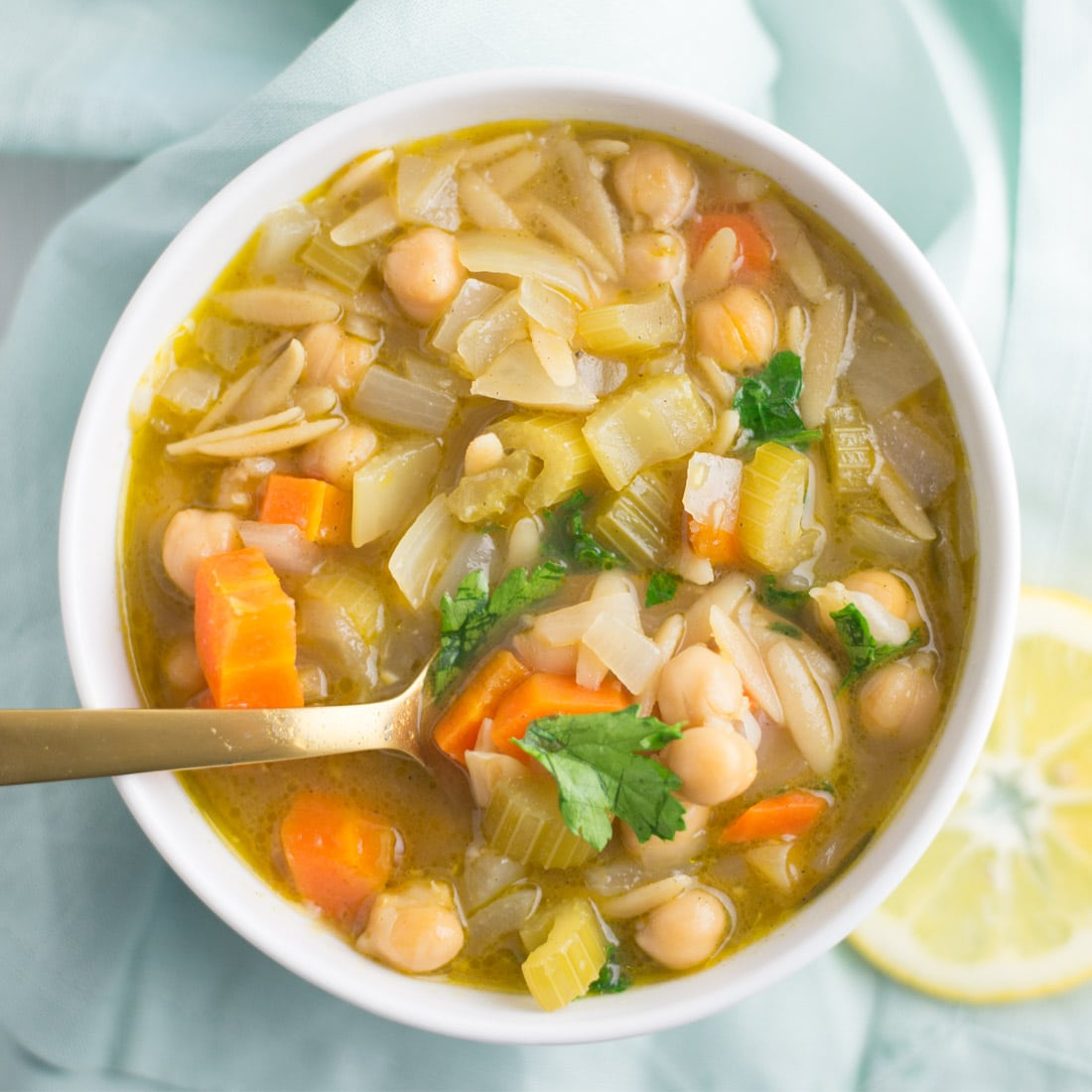 bowl of orzo lemon soup with chickpeas with gold spoon on blue napkin with lemon slice