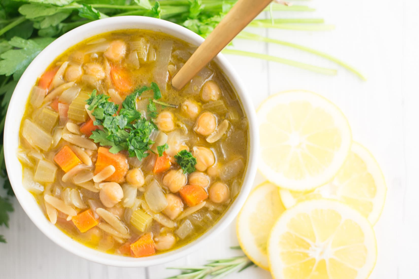 bowl of orzo lemon soup with chickpeas with gold spoon on white background with lemon slices and parsley