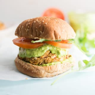 veggie quinoa burger with lettuce, tomato, and pesto on hamburger bun