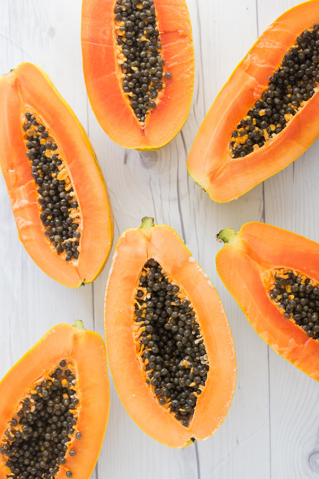 papaya halves on a white wood background.