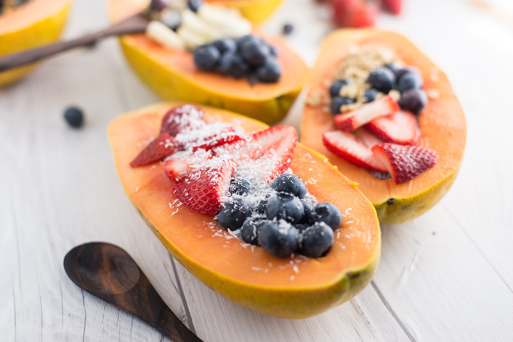 papaya boats with blueberries, strawberries, shredded coconut on a white wood background