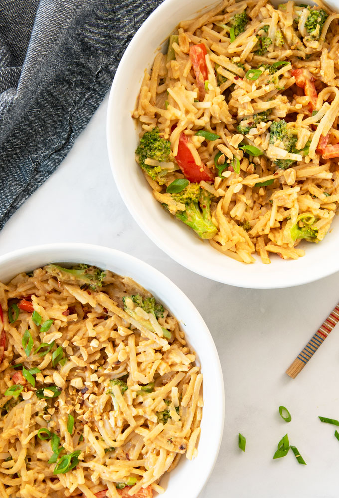 two bowls of peanut noodles with broccoli and red bell pepper