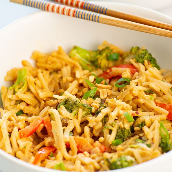 peanut noodles in a bowl with chopsticks
