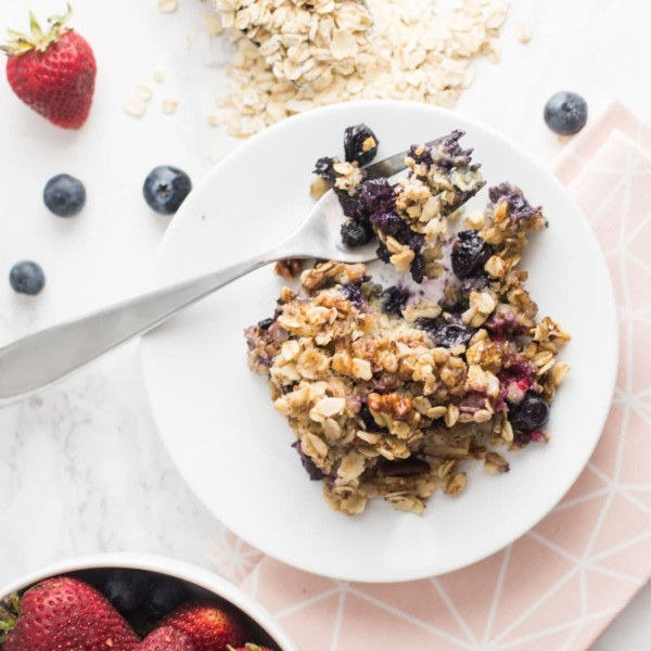 baked oatmeal with fresh berries on white plate with fork on marble table