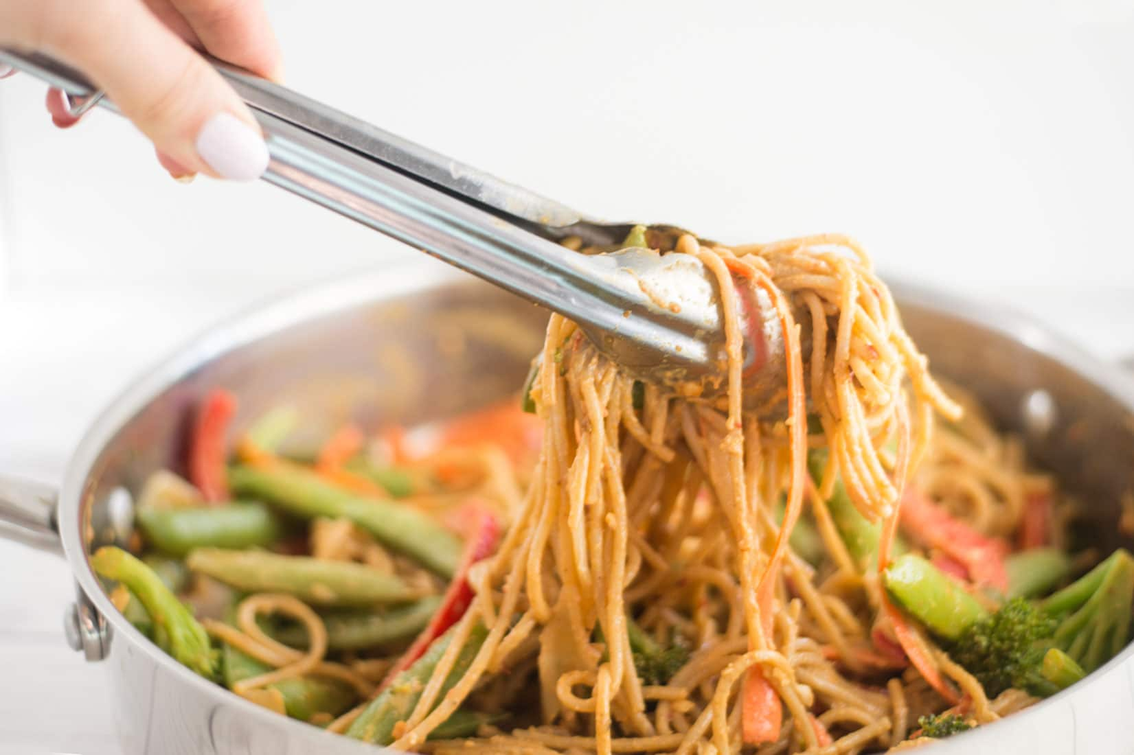 hand using tongs to grab peanut noodles out of pan