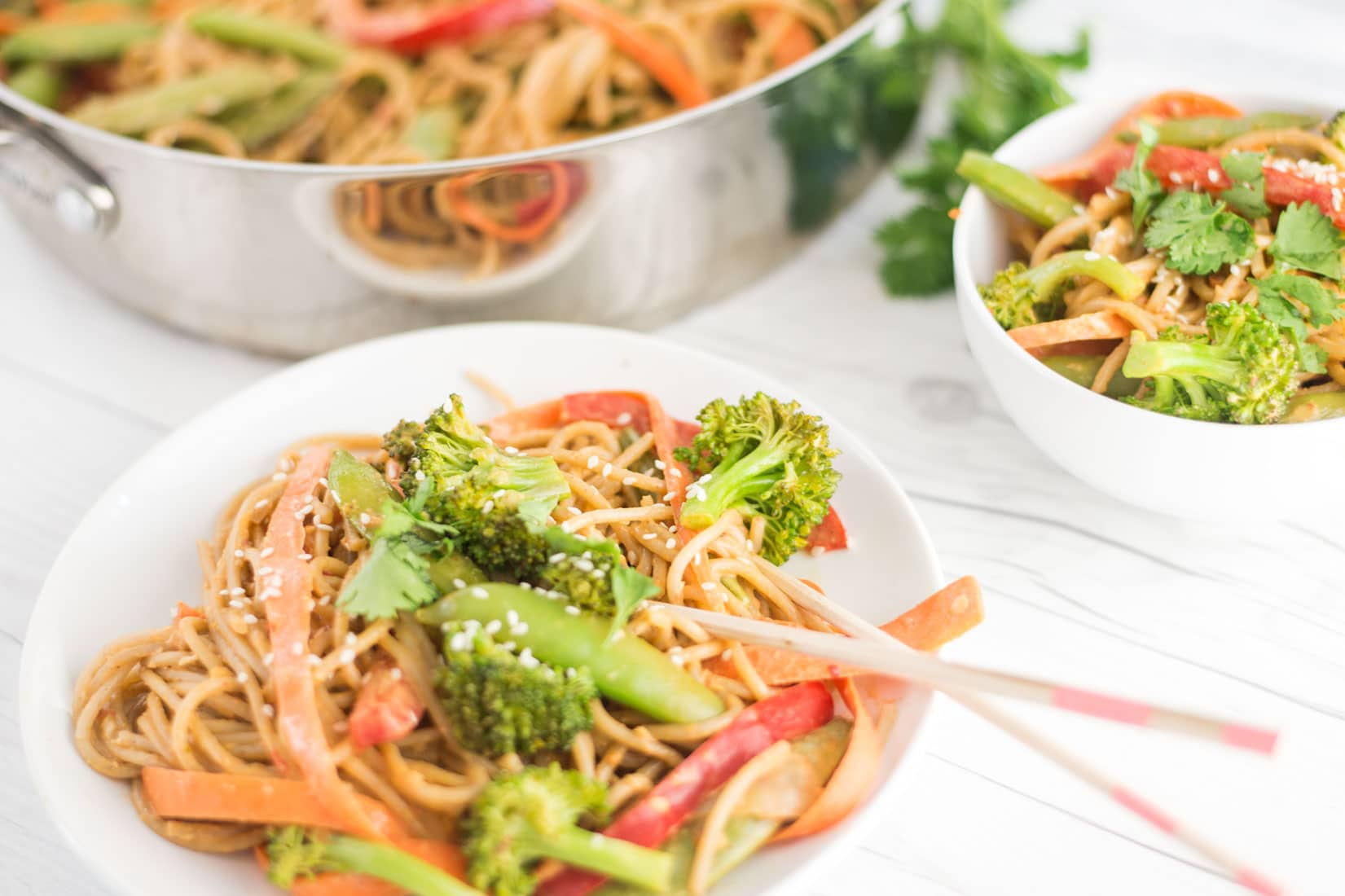 white bowl of peanut noodles with vegetables and chopsticks