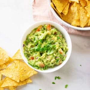 bowl of guacamole on white background with tortilla chips