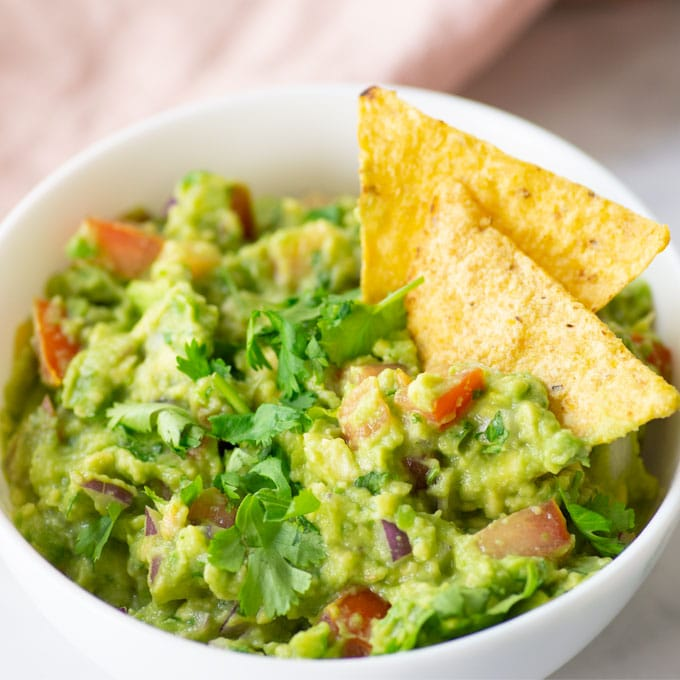 bowl of guacamole topped with cilantro with two tortilla chips in bowl