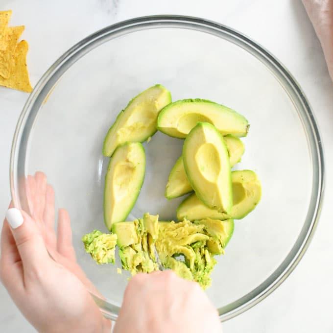 hand mashing avocados in mixing bowl