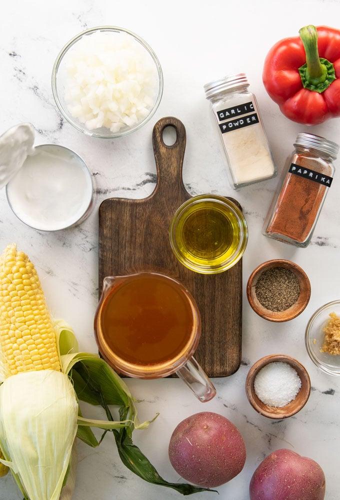 ingredients for vegan corn chowder on white background