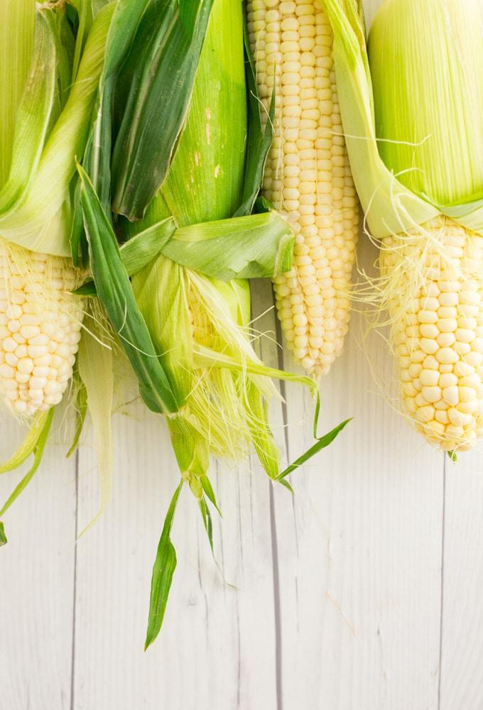 fresh corn on the cob on white wood background