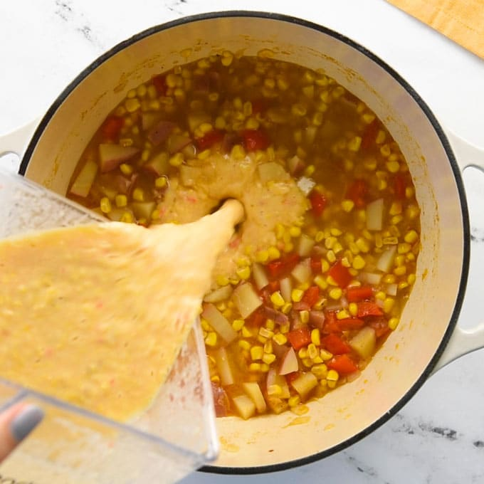 pouring soup from a blender into a soup pot