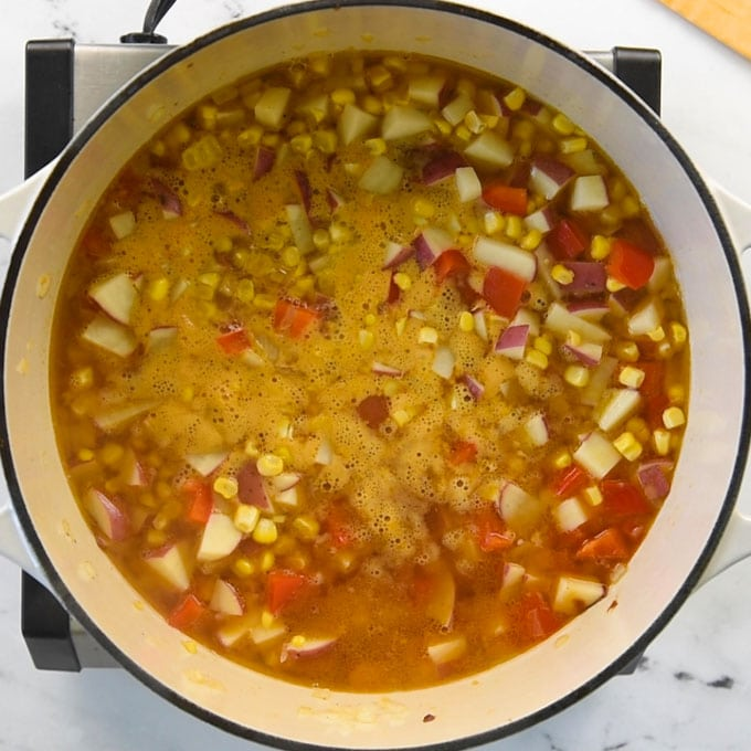 ingredients for corn chowder in a soup pot simmering