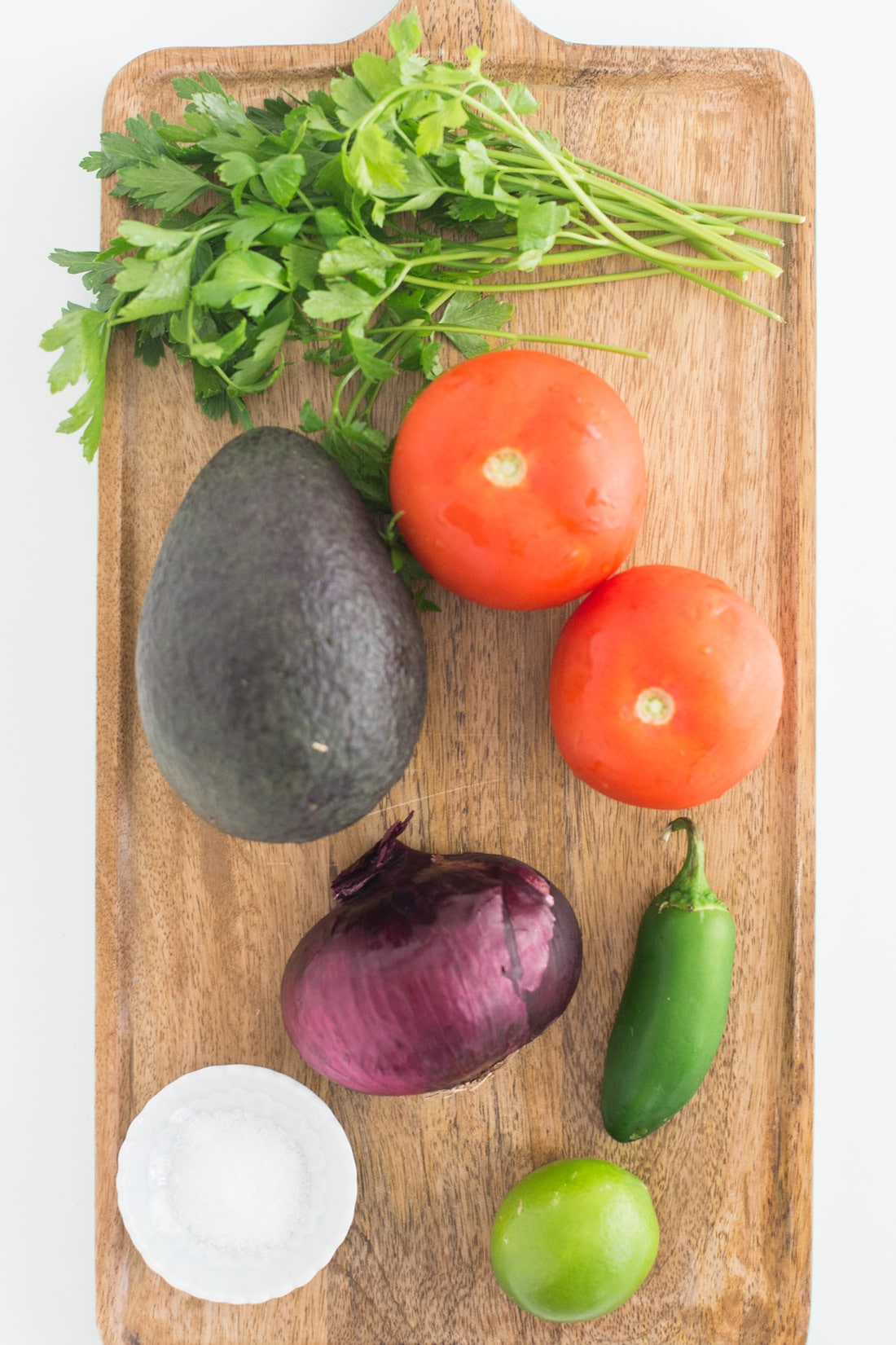 wooden board with avocado, cilantro, red onion, salt, lime, jalapeno, and tomatoes