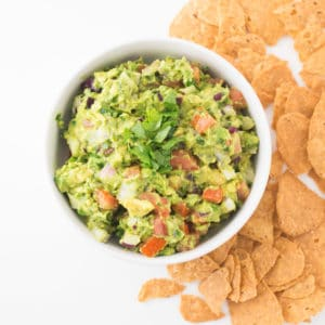 bowl of guacamole on white counter with tortilla chips