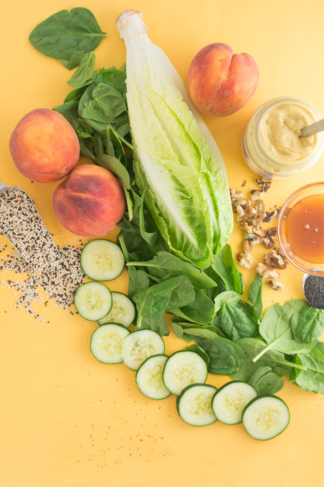spinach, romaine, peaches, quinoa, walnuts, poppy seeds, honey, and mustard on yellow background