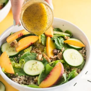 hand pouring honey poppyseed dressing over peach salad on yellow background