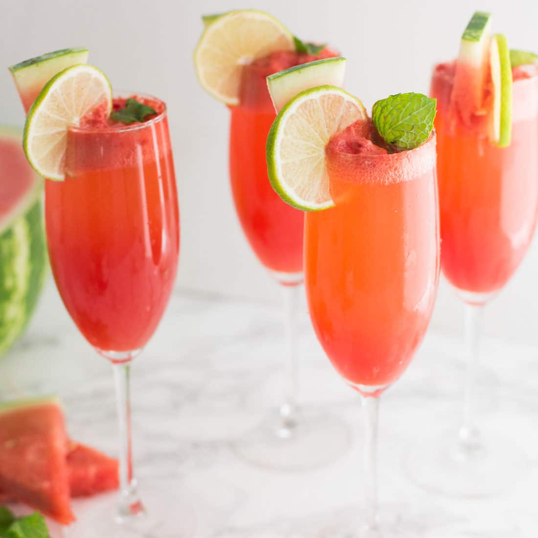 watermelon mimosas garnished with mint and lime on marble counter