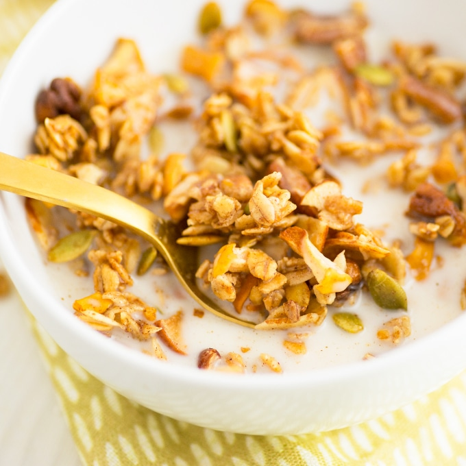 spoon with apple spice granola in bowl with milk