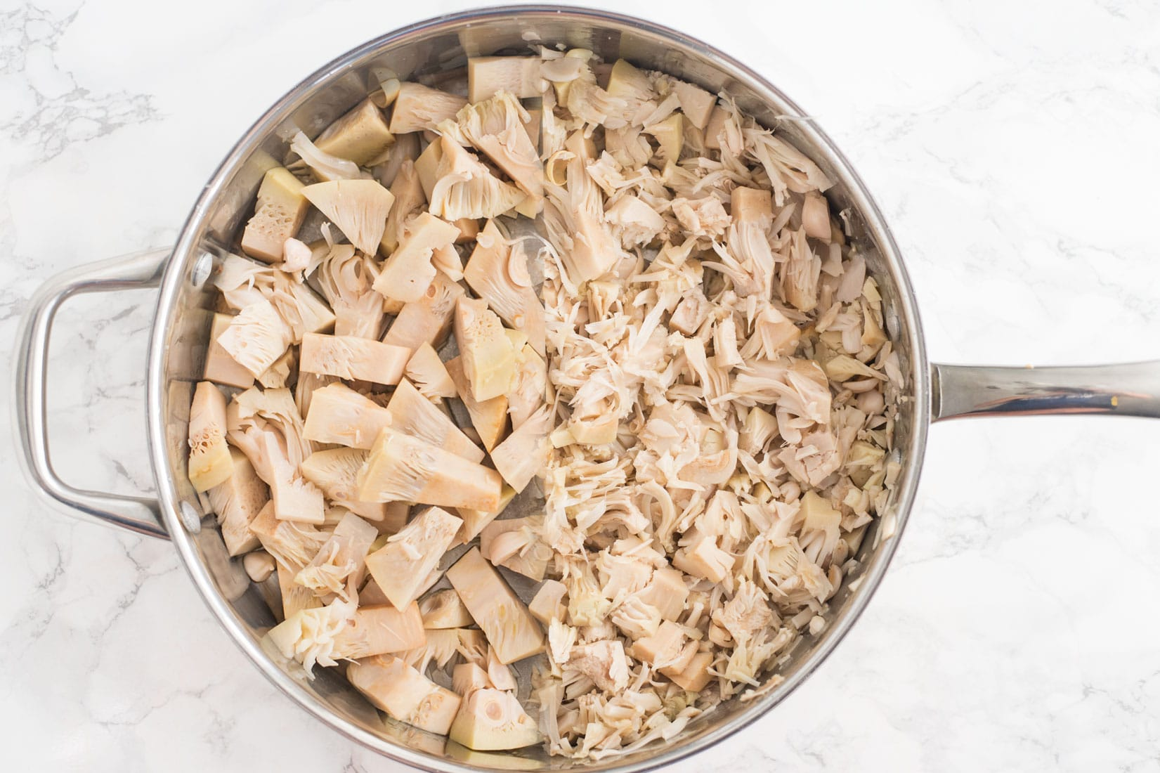 canned jackfruit in large sautee pan on marble counter
