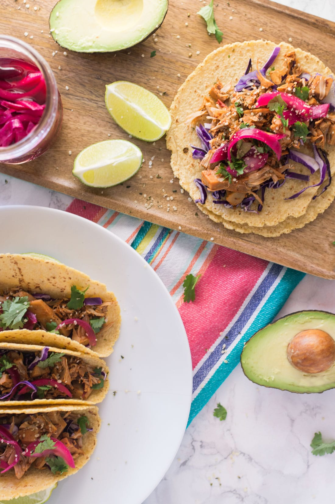 vegan jackfruit pulled pork tacos with limes, avocado, and red onions on marble counter