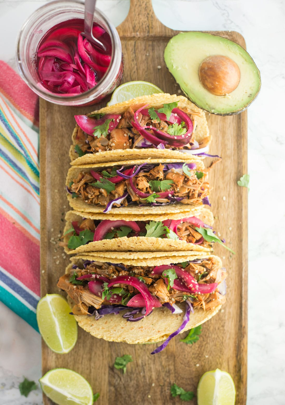 vegan jackfruit pulled pork tacos on wooden board with pickled red onions, avocado, lime wedges, and cilantro with colorful napkin on marble counter