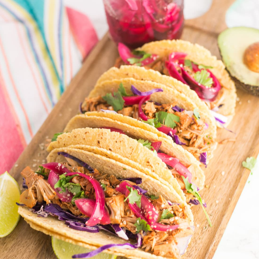 vegan jackfruit pulled pork tacos on wood board with avocado, limes, and pickled red onions