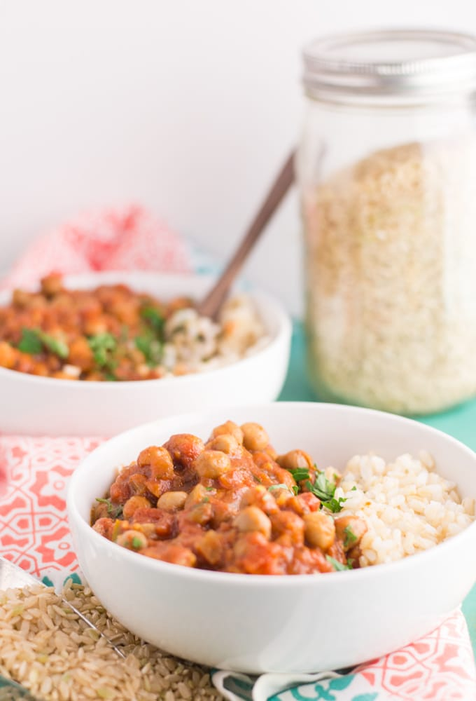 two bowls of vegan slow cooker chana masala with rice and cilantro