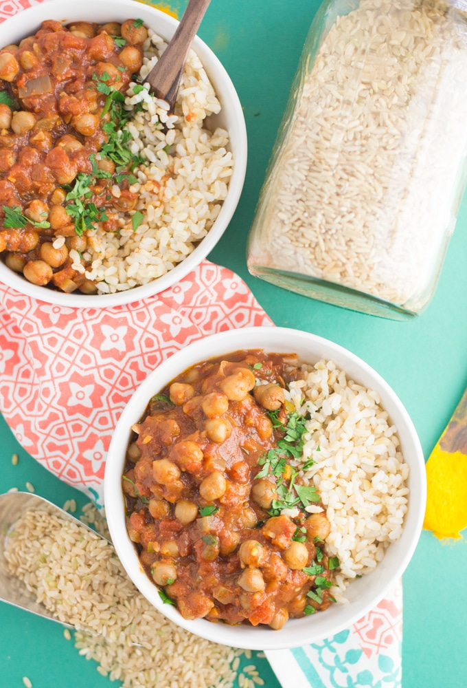 two bowls of vegan chana masala - easy and healthy dinner on green background with brown rice and turmeric