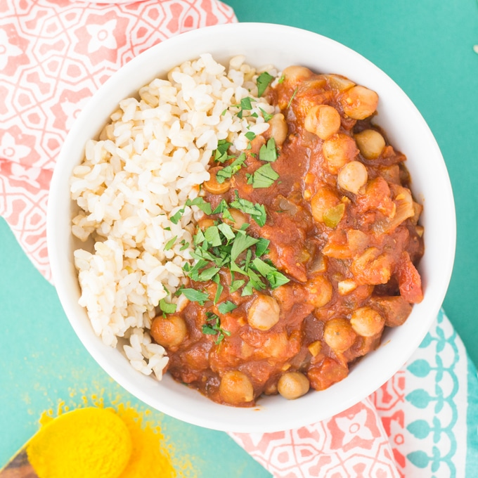 slow cooker chana masala in white bowl with rice and cilantro