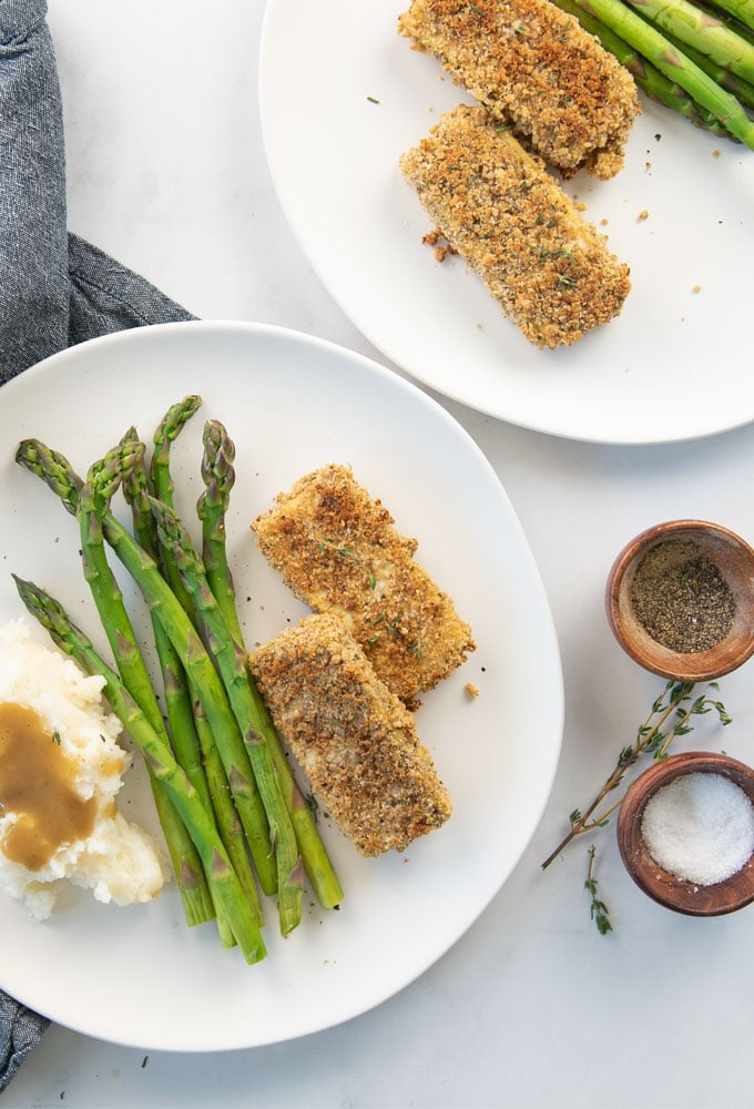 breaded tofu on a plate with asparagus and mashed potatoes