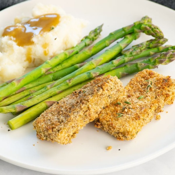 closeup of breaded tofu on a plate with vegetables and mashed potatoes