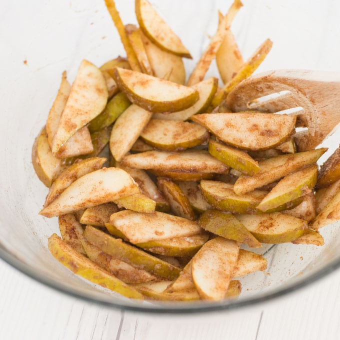 pear slices and cinnamon in mixing bowl