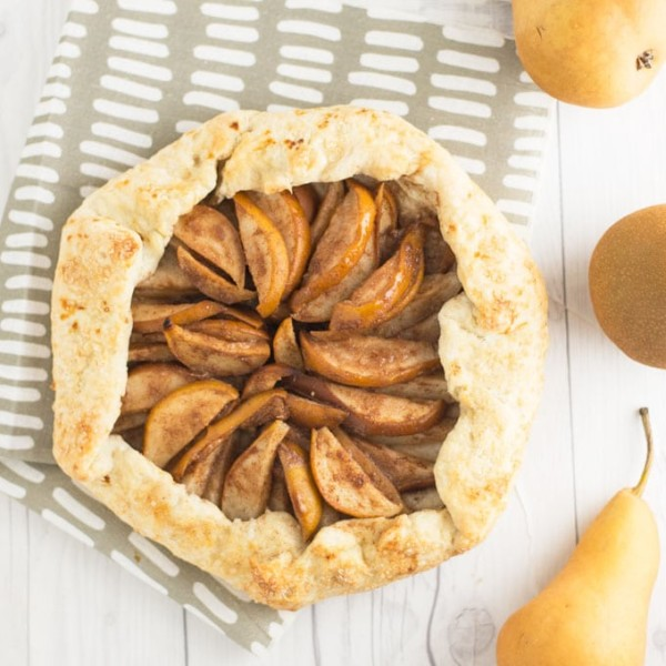 vegan pear galette with grey napkin on white background