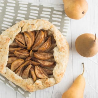 Vegan Pear Galette -- This vegan galette is made up of a perfectly flakey pie crust and piled high with cinnamon ginger pear slices. Baked to perfection, you won't believe how simple this dessert recipe is to make. | mindfulavocado