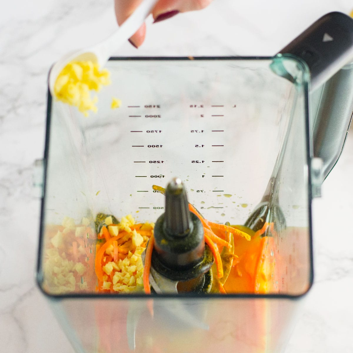 pouring ginger into blender of orange juice, carrots, and turmeric