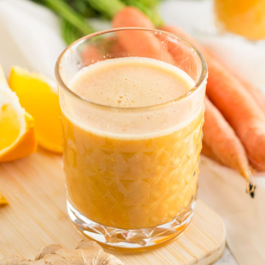orange smoothie, orange slices, ginger on cutting board with carrots and spoonful of turmeric