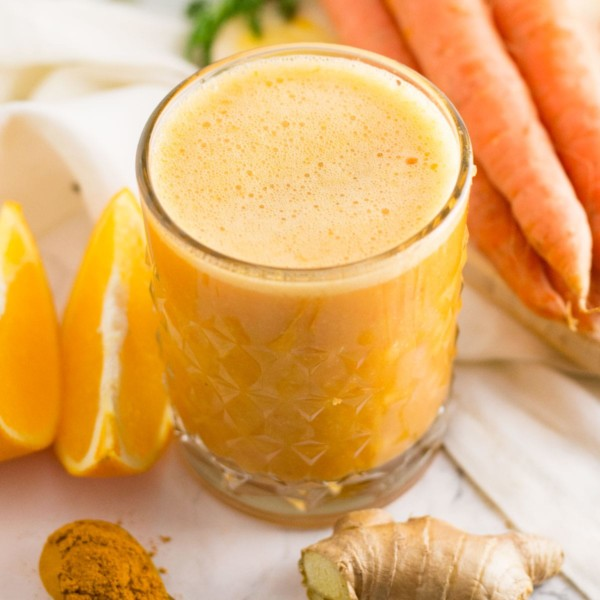 orange smoothie with prange slices, carrots, ginger, and turmeric