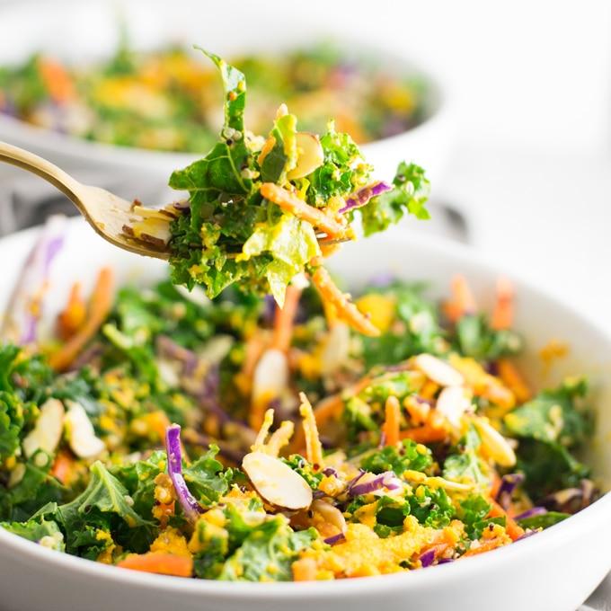 fork holding kale over salad bowl