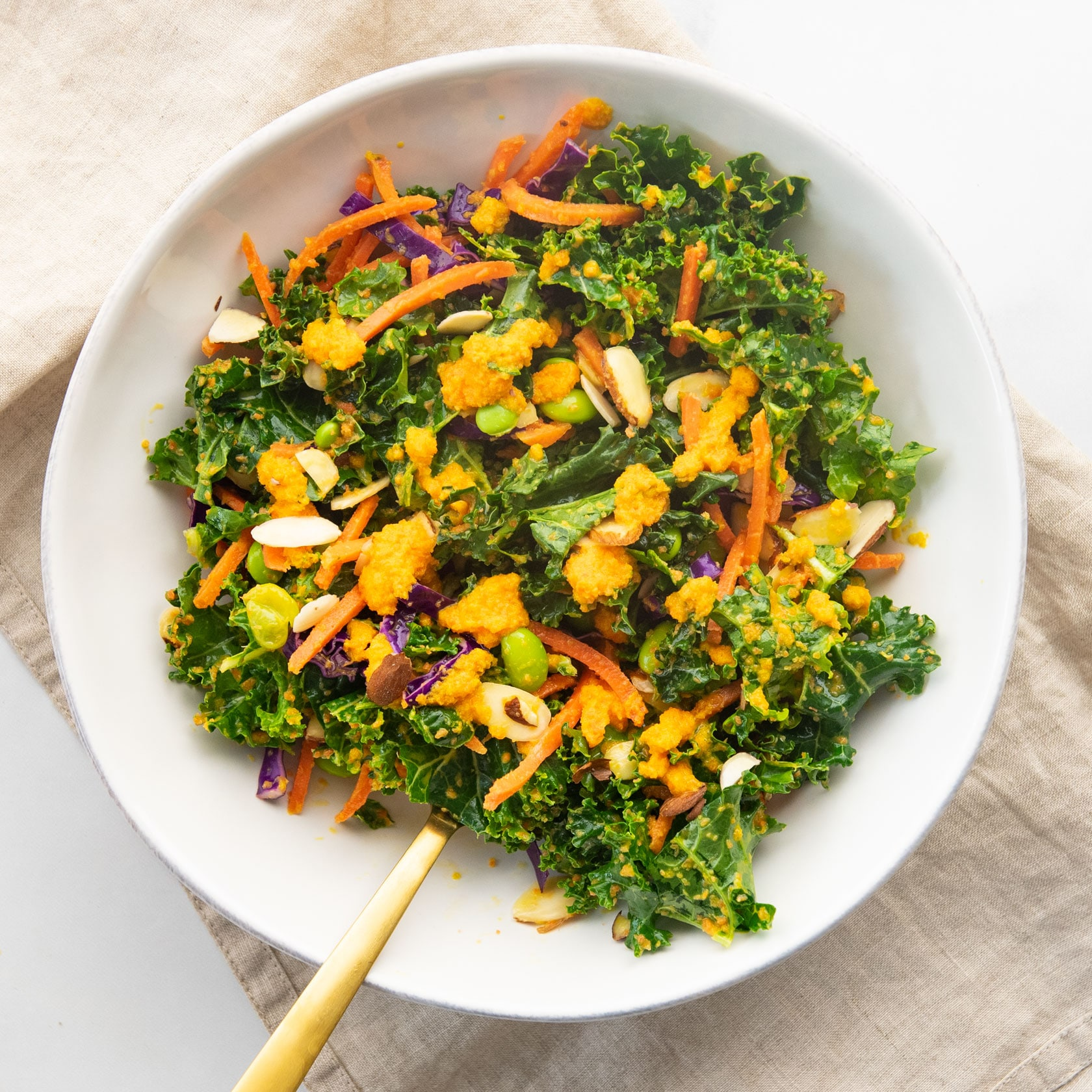 overhead view of kale salad with carrot ginger dressing