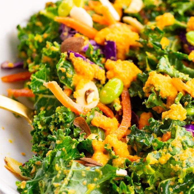 closeup of asian kale salad with carrots, cabbage, and edamame