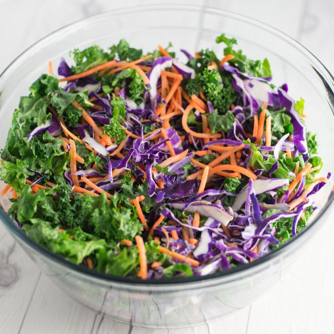 kale, shredded carrots, purple cabbage in glass bowl