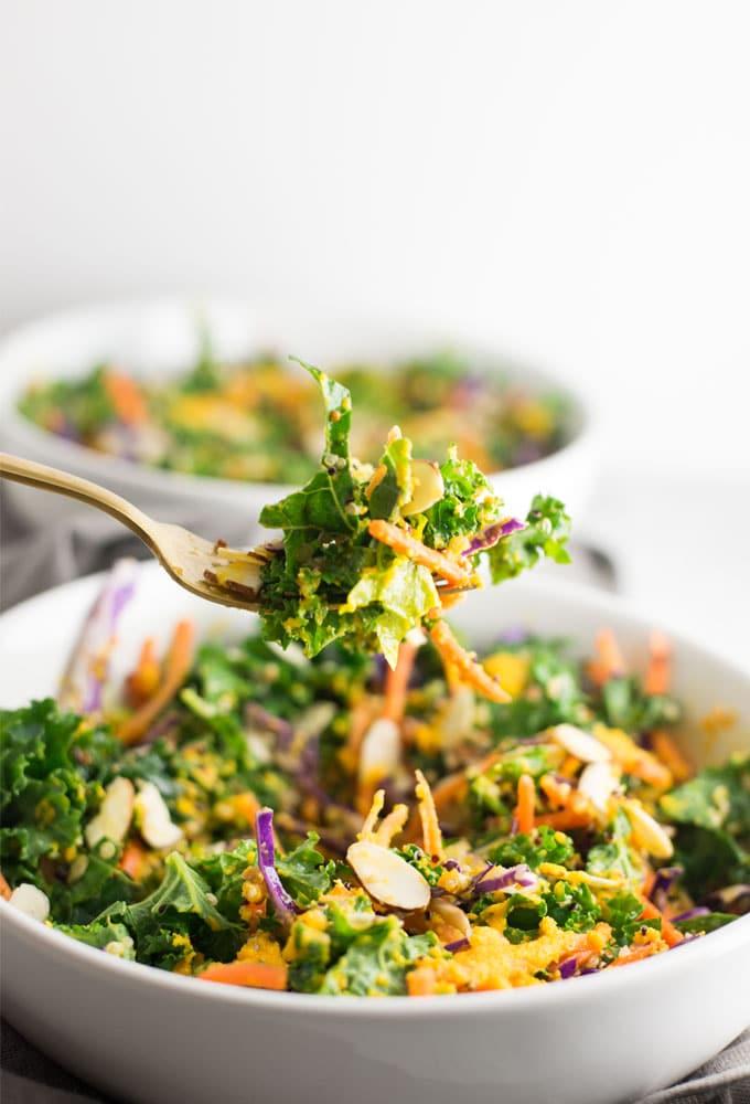 fork over big bowl of kale salad with carrot ginger dressing