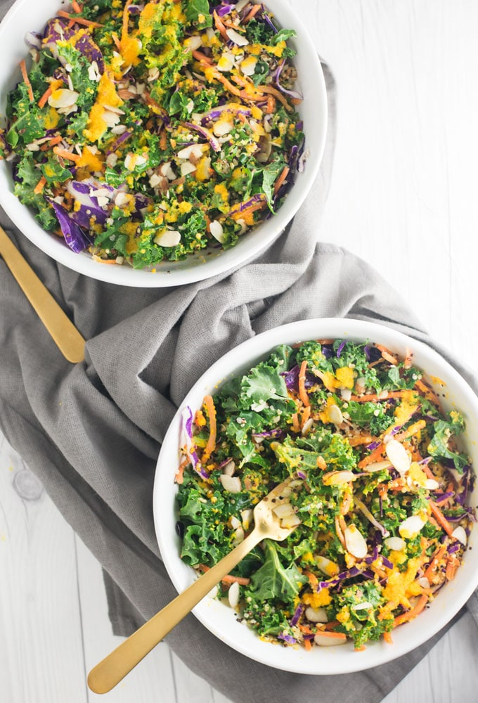 two big bowls of kale salad with gold forks on grey linen napkin