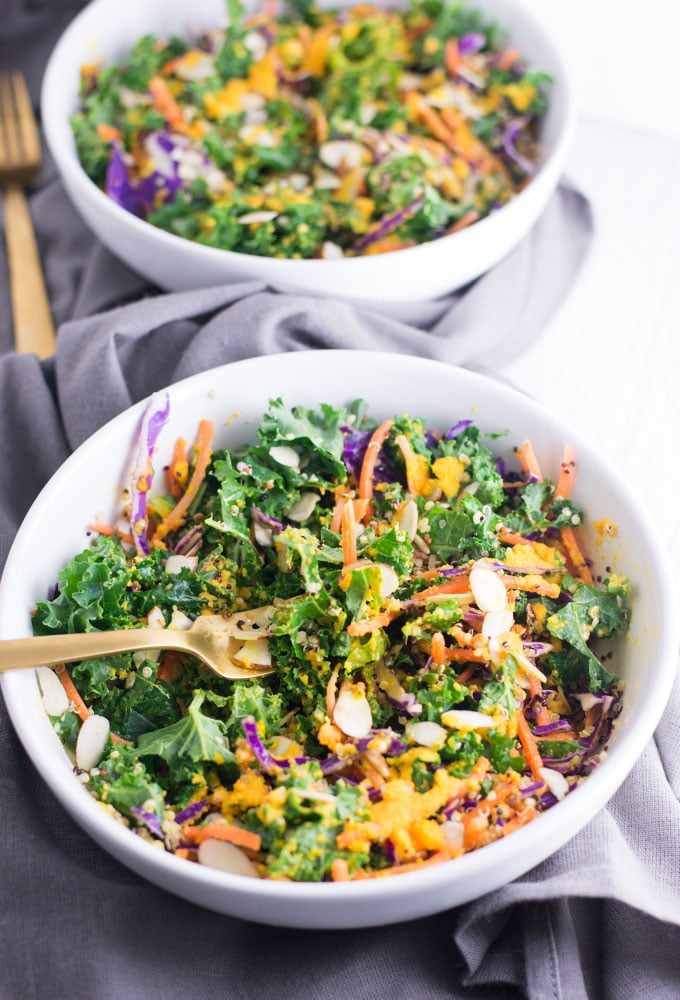 two bowls of kale salad with carrot ginger dressing on a grey linen napkin