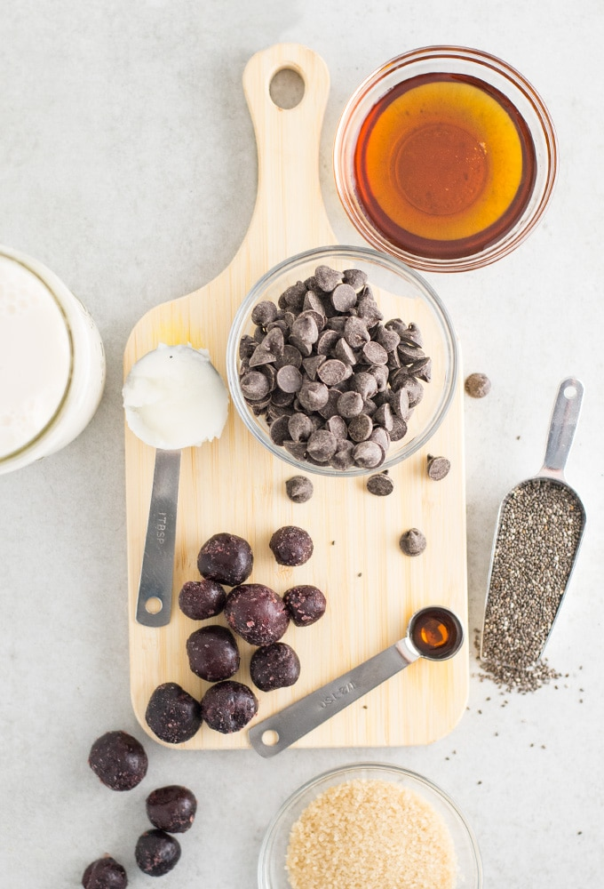 maple syrup, chocolate chips, coconut oil, cherries, almond milk, vanilla extract, cane sugar, and chia seeds on wooden cutting board on light grey background
